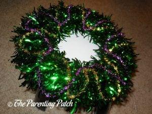 Adding Purple Beads to Green Tinsel Mardi Gras Wreath