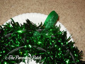 Adding the Green Ribbon Hanger to Green Tinsel Mardi Gras Wreath