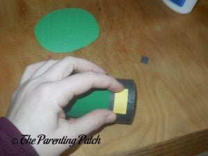 Gluing the Yellow Rectangle to the Toilet Paper Roll Leprechaun Hat Craft