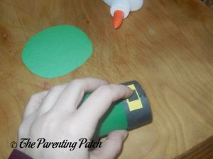 Gluing the Black Rectangle to the Toilet Paper Roll Leprechaun Hat Craft