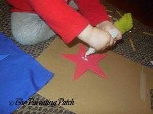 Gluing the Foam Stars of the Seedling Design Your Own Superhero Cape