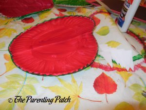 Folding the Red and Green Plate for A Is for Alligator Paper Plate Craft