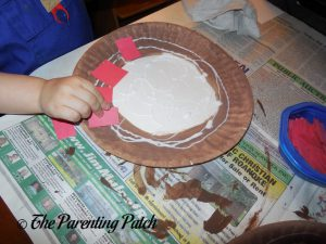 Gluing Red Squares on the P Is for Pizza Paper Plate Craft