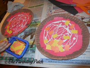 Gluing Orange and Yellow Squares on the P Is for Pizza Paper Plate Craft