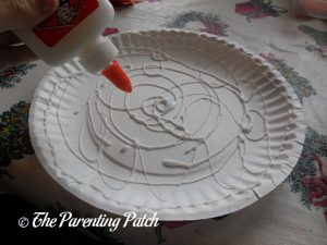 Pouring Glue on the P Is for Pumpkin Paper Plate Craft