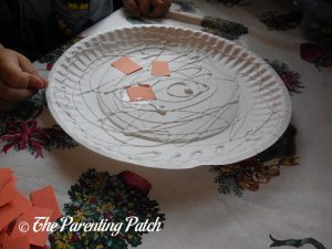 Gluing Orange Squares on the P Is for Pumpkin Paper Plate Craft