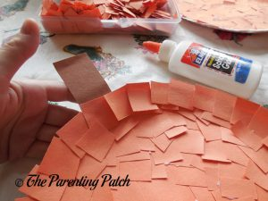Gluing the Stem on the Pumpkin Paper Plate Craft