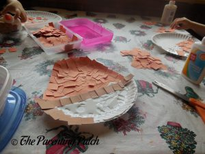 Gluing Brown Squares on the A Is for Acorn Paper Plate Craft
