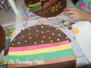 Adding Yellow Paint Seeds to the H Is for Hamburger Paper Plate Craft