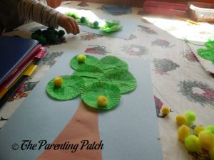 Gluing Pompom Apples on the Cupcake Liner Apple Tree Craft