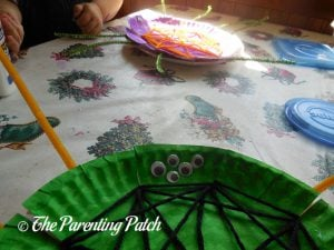 Gluing Eyes on the S Is for Spider Halloween Paper Plate Craft