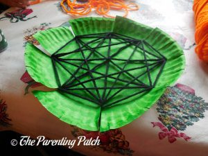 Weaving the Yarn on the S Is for Spider Halloween Paper Plate Craft