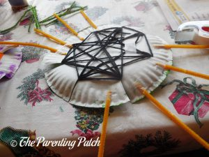 Taping Pipe Cleaners on the S Is for Spider Halloween Paper Plate Craft