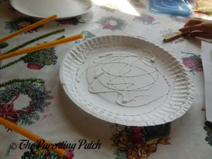 Putting Glue on a Plate for the S Is for Spider Halloween Paper Plate Craft