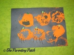 Apple Print Pumpkin Jack-o-Lantern Halloween Craft by Preschooler