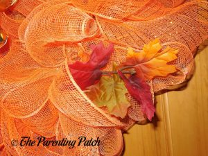 Adding Leaves to the Deco Mesh and Burlap Ribbon Autumn Pumpkin Wreath Craft