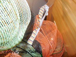 Adding the Ribbon Hanger to the Deco Mesh and Burlap Ribbon Autumn Pumpkin Wreath Craft