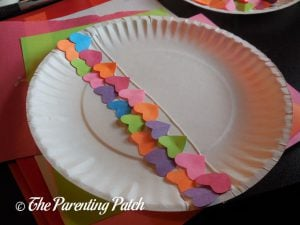 Gluing Small Hearts on the Heart Fish Valentine's Day Paper Plate Craft
