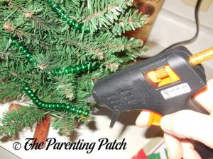 Gluing the Beads on the Upcycled Beaded Christmas Tree Craft